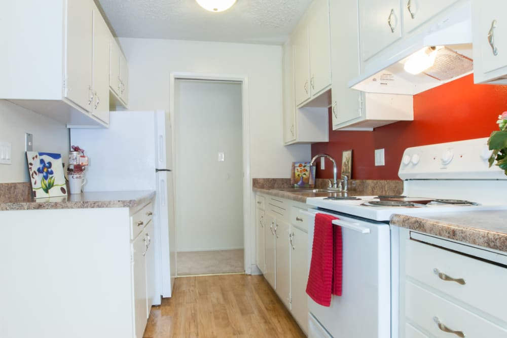 Kitchen with wood style flooring at Del Coronado Apartments in Alameda, California