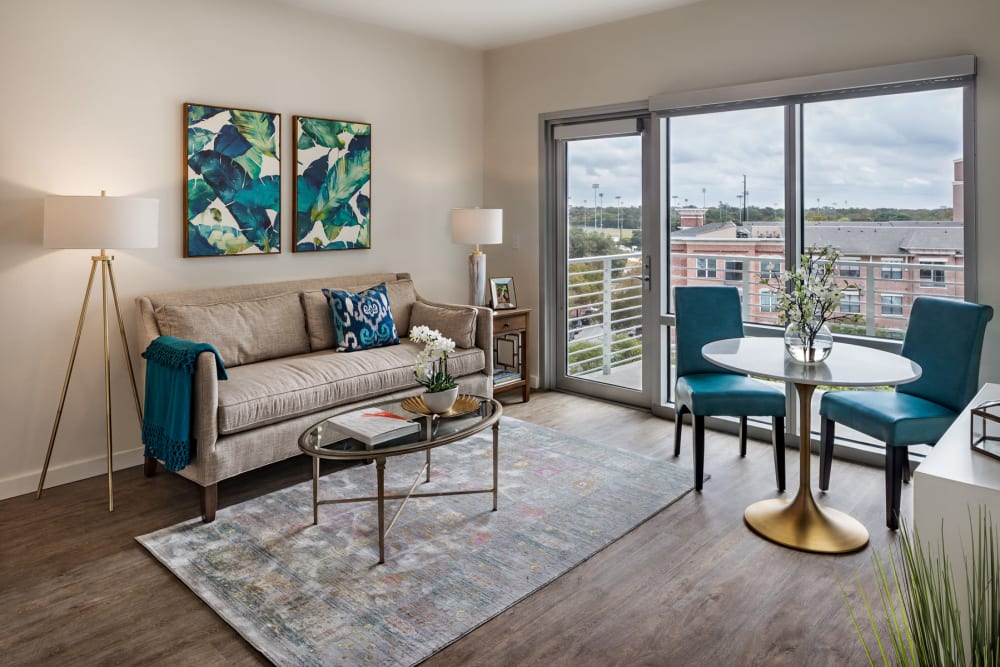 An apartment living room and doors to the balcony at The Village at The Triangle in Austin, Texas