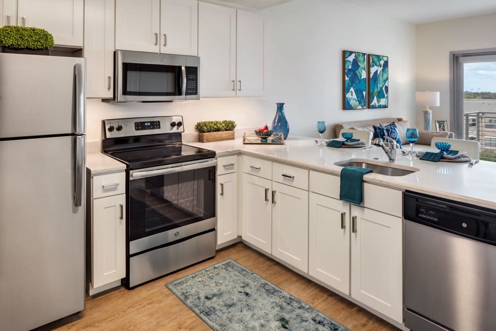 An apartment kitchen with stainless steel appliances at The Village at The Triangle in Austin, Texas