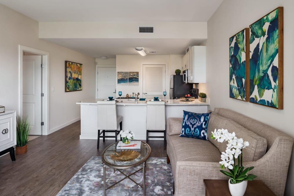 An apartment kitchen and  living room with wood flooring at The Village at The Triangle in Austin, Texas