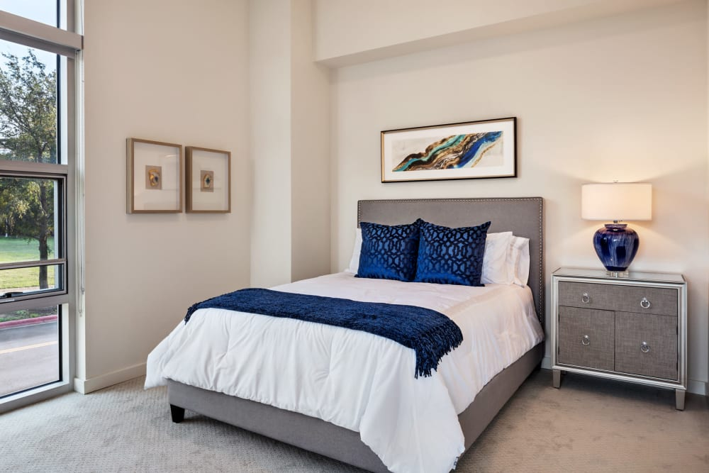 An apartment bedroom with large windows at The Village at The Triangle in Austin, Texas