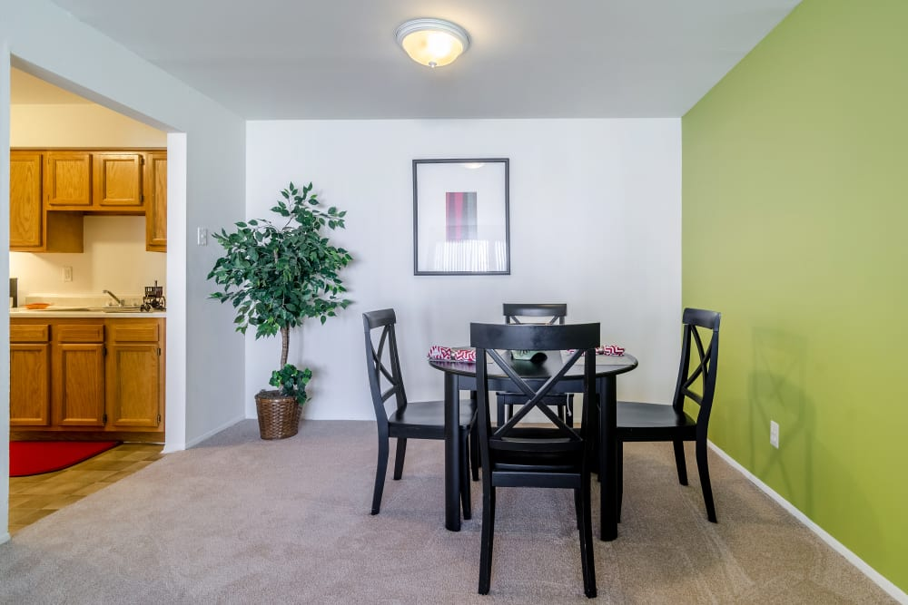 Dining table near kitchen in model at Edgewood Park Apartments in Pontiac, Michigan