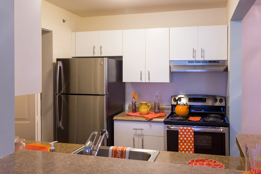 Kitchen with orange accents at Waters Edge Apartments in Lansing, Michigan