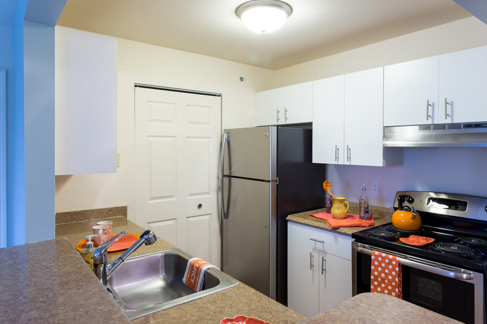 Kitchen with black appliances at Waters Edge Apartments in Lansing, Michigan