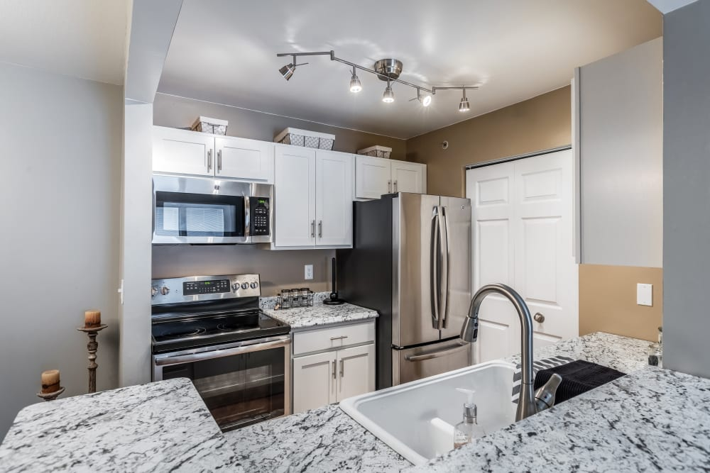 Kitchen with granite counter-tops at Waters Edge Apartments in Lansing, Michigan
