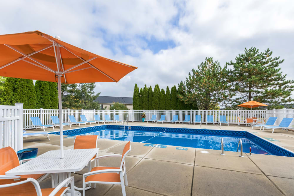 Outdoor pool with patio seating at Waters Edge Apartments in Lansing, Michigan