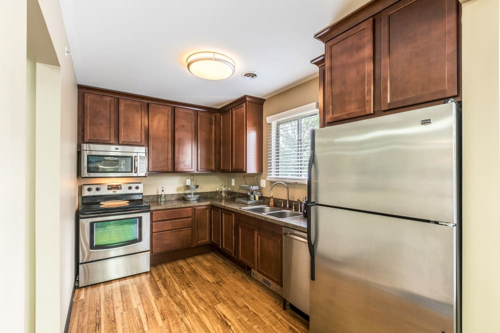 Kitchen with wood cabinetry at Waters Edge Apartments in Lansing, Michigan