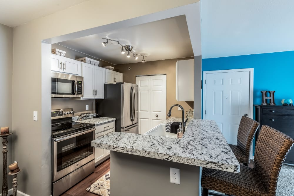 Kitchen with blue accent wall at Waters Edge Apartments in Lansing, Michigan