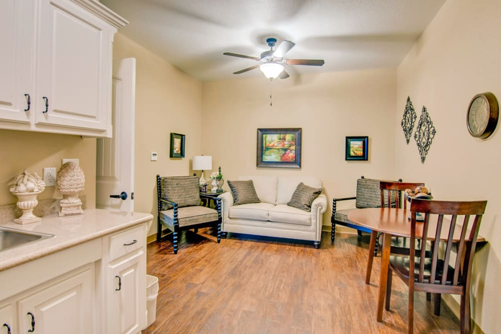 An apartment kitchen and living room at Village on the Park Bentonville in Bentonville, Arkansas