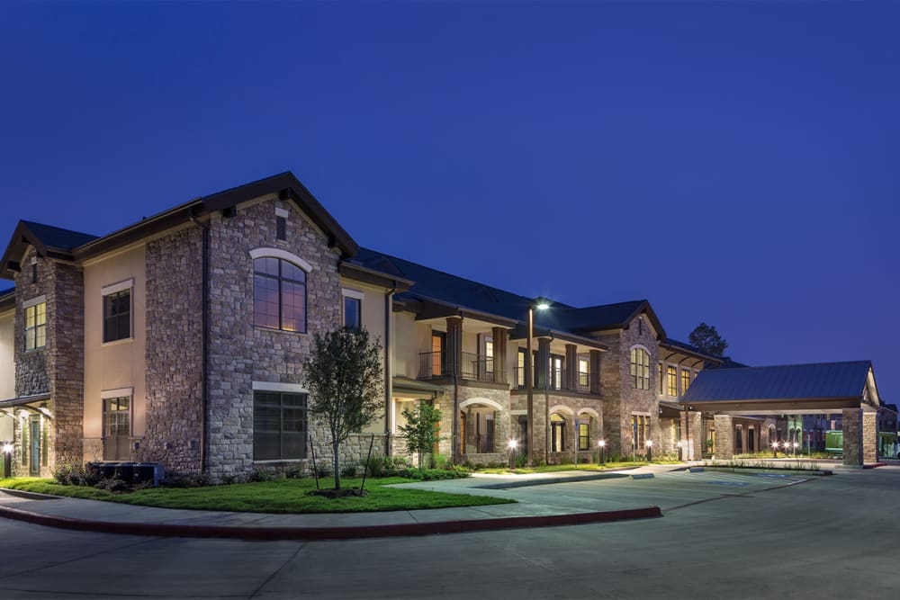 The building exterior at night with the lights on at Spring Creek Village in Spring, Texas