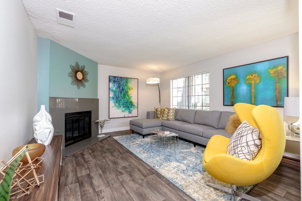 Living room layout with yellow chair and blue accents at Sonora at Alta Loma in Alta Loma, California