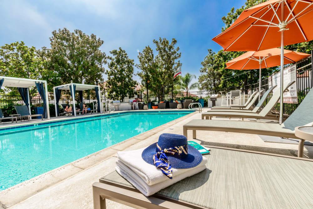 Swimming pool with orange umbrellas at Sonora at Alta Loma in Alta Loma, California