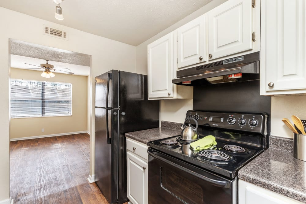 Bright kitchen with black appliances at Carriage Hills in Macon, Georgia