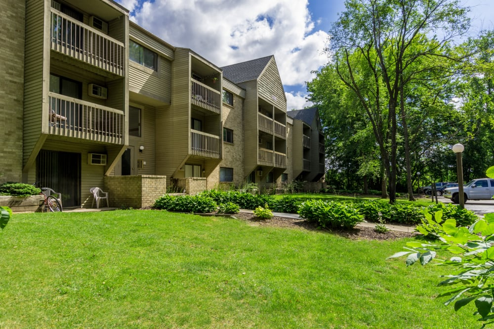 Large trees and open grass areas around Kellogg Cove Apartments in Kentwood, Michigan