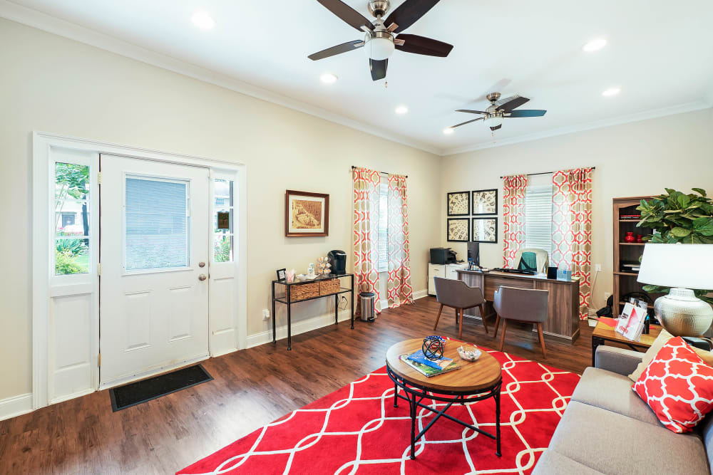 Living room with ceiling fan and red rugs at The Grove at Six Hundred in Rome, Georgia