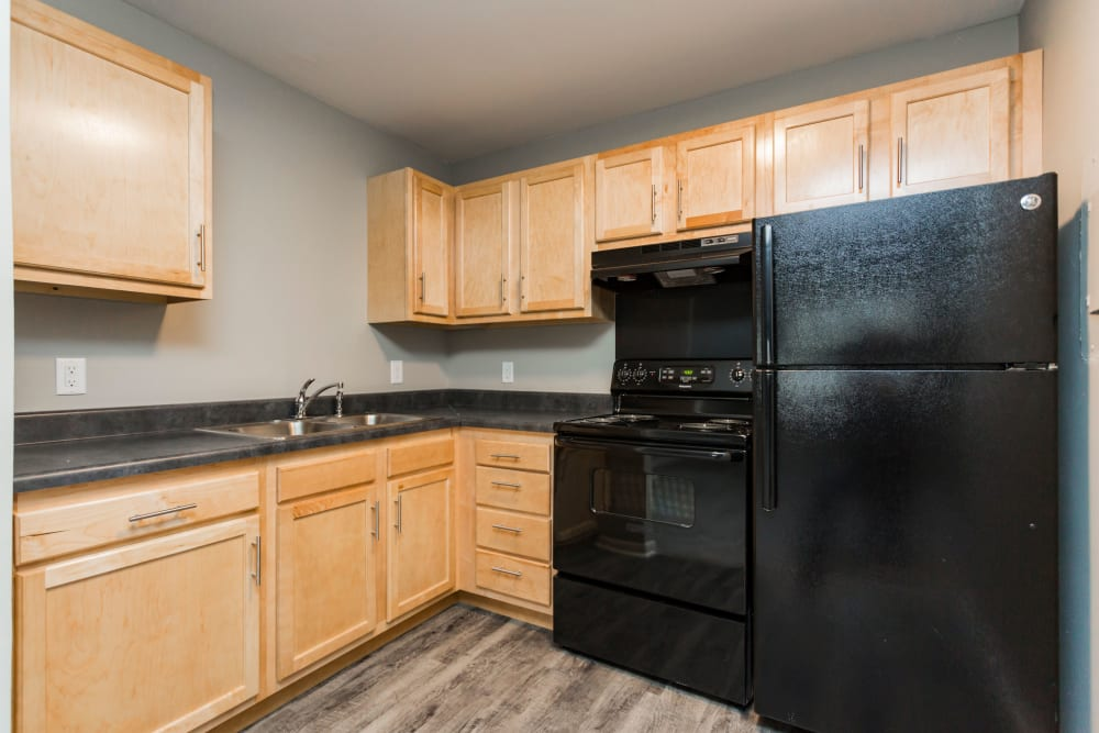 Kitchen with black appliances at Gibson Creek Apartments in Madison, Tennessee