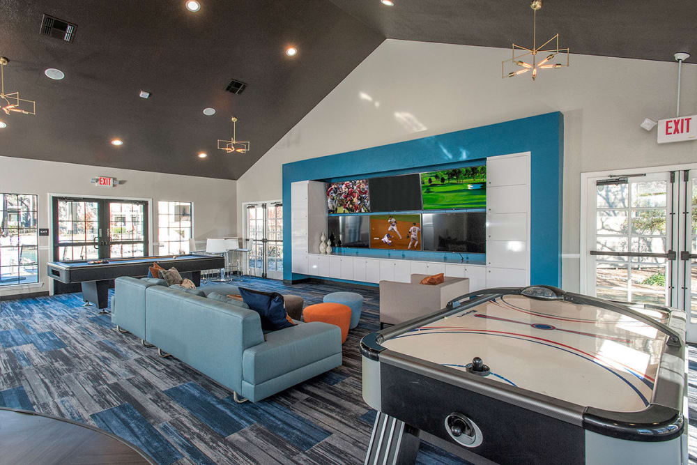 Flatscreen TVs and air hockey in the resident clubhouse game room at Slate Creek Apartments in Roseville, California