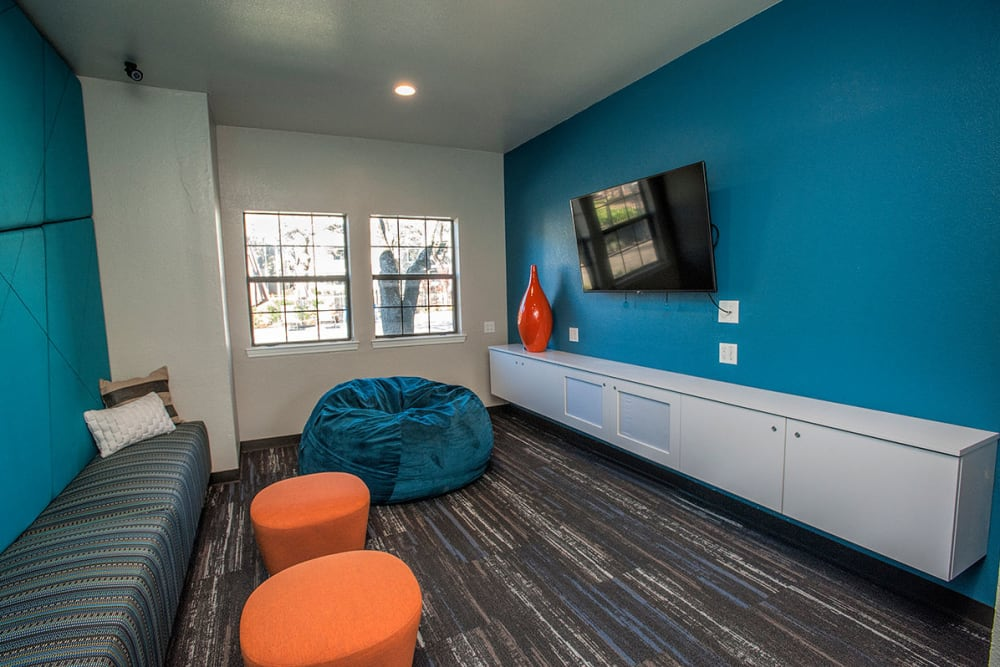 Lounge seating and flatscreen TVs in the resident clubhouse at Slate Creek Apartments in Roseville, California
