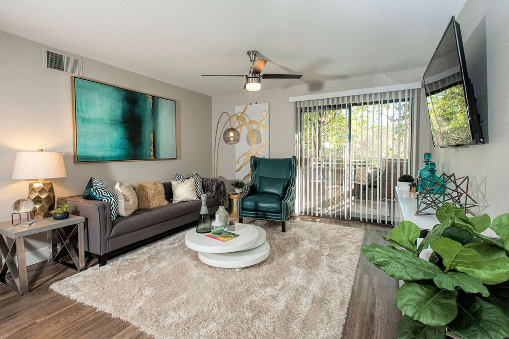 Model home's living area with hardwood floors and a sliding door leading to the private patio outside at Slate Creek Apartments in Roseville, California
