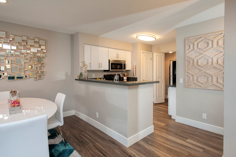 Partial view of the dining area looking over the breakfast bar into the kitchen of a model home at Slate Creek Apartments in Roseville, California