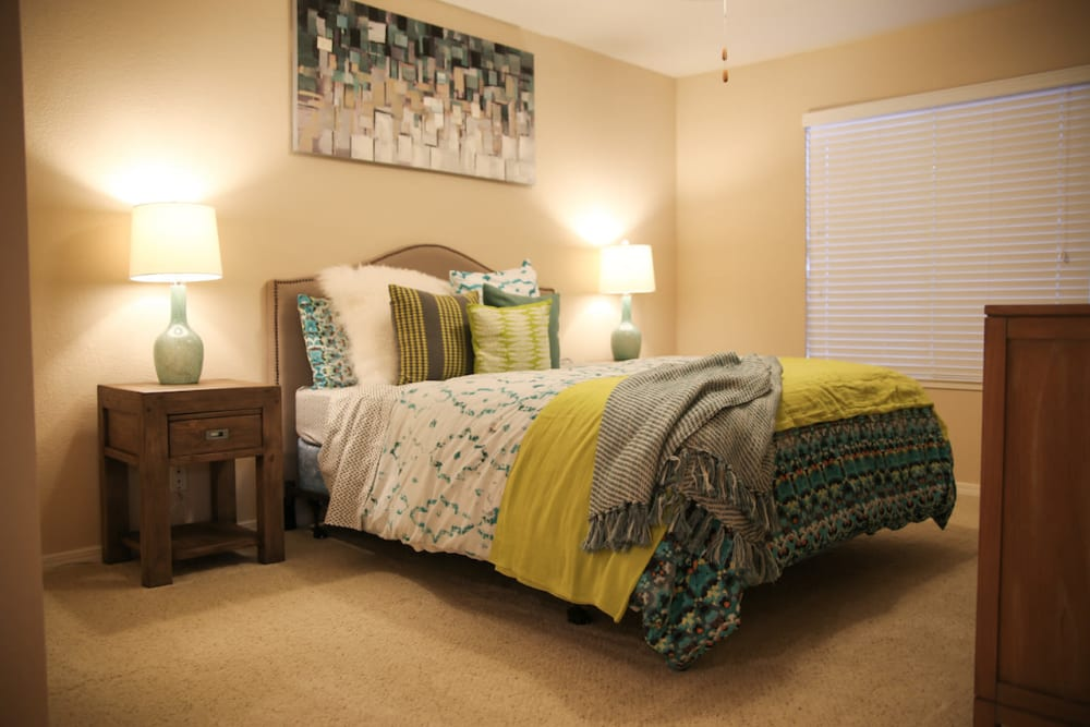 Bright and well-decorated model home's bedroom at Slate Creek Apartments in Roseville, California