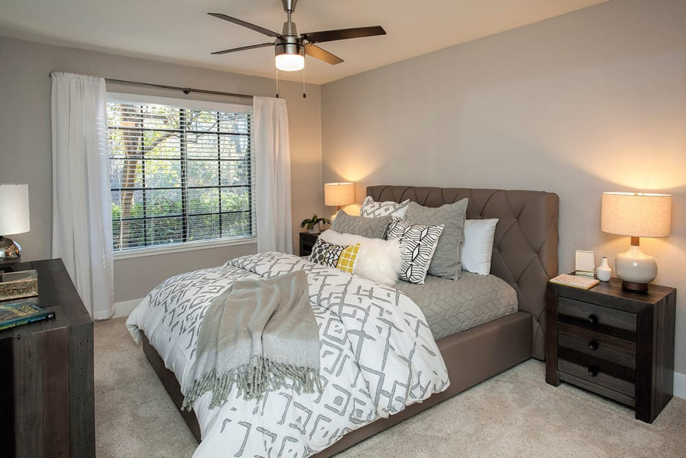 Ceiling fan and large windows in a model home's bedroom at Slate Creek Apartments in Roseville, California