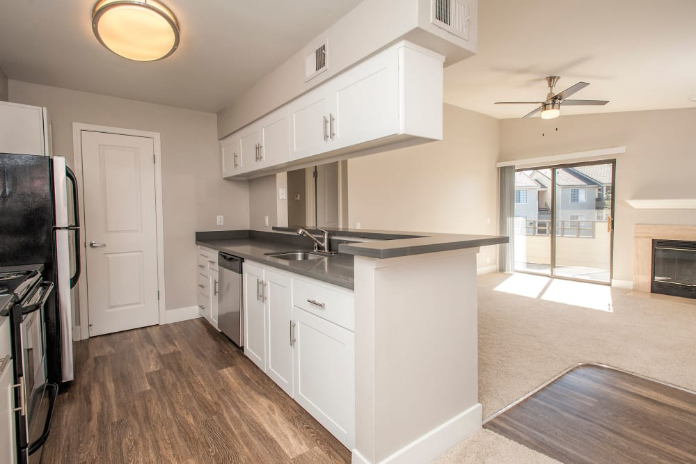 Hardwood floors and white cabinetry in a model home's kitchen at Slate Creek Apartments in Roseville, California