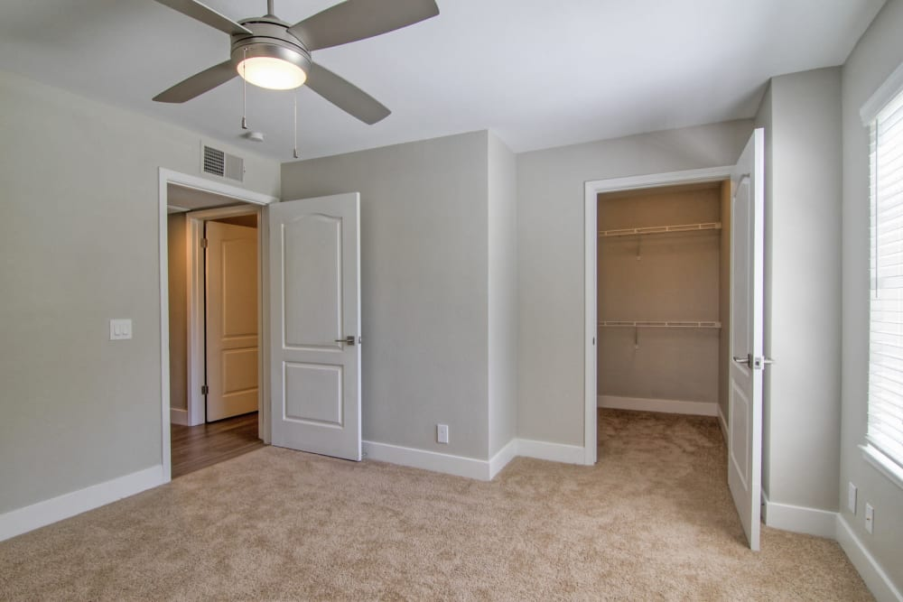 Ceiling fan and a walk-in closet in a model home's bedroom at Slate Creek Apartments in Roseville, California
