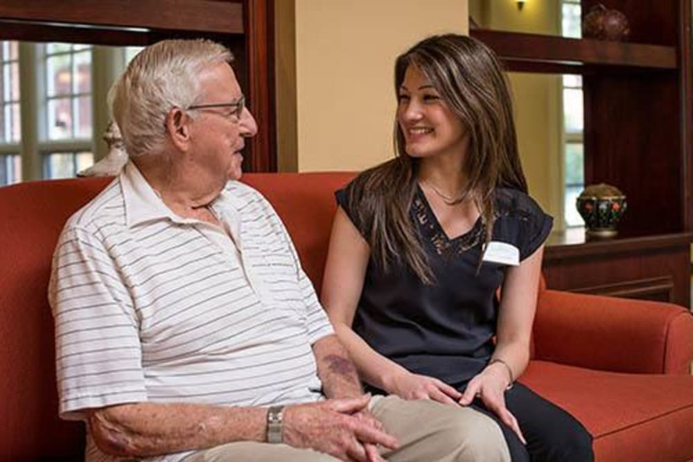 Resident talking to a caregiver at WellQuest of Menifee Lakes in Menifee, California