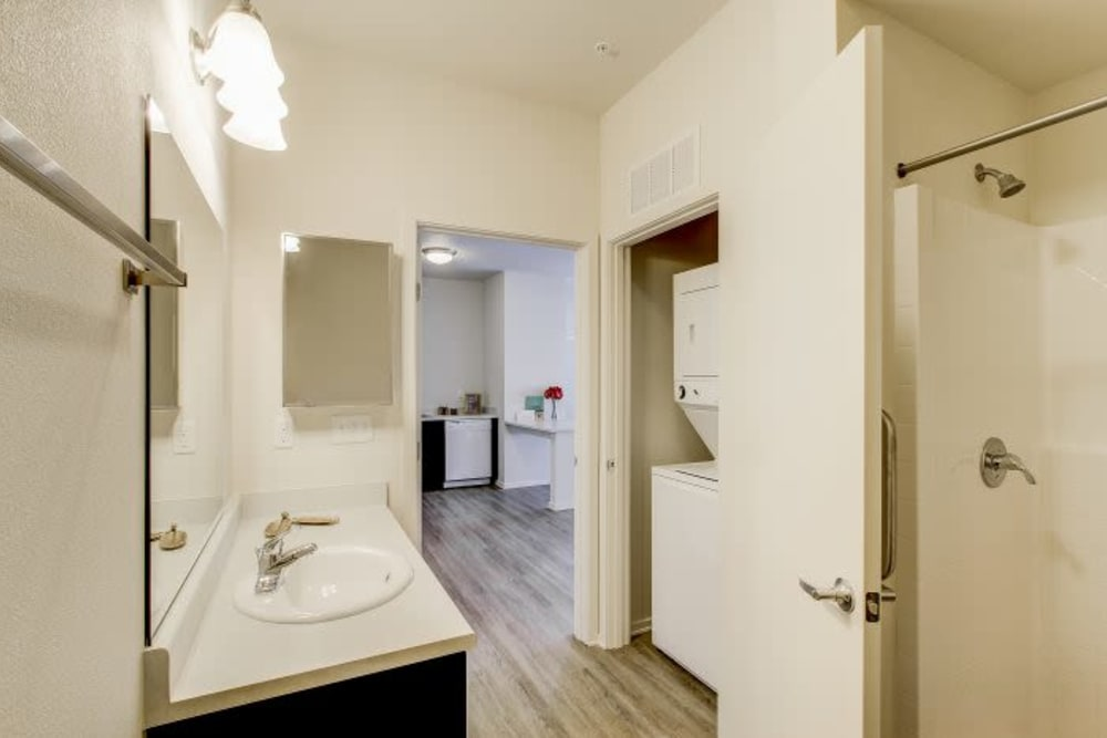 Bathroom with a washer and dryer and vanity mirror at LARC at Kent in Kent, Washington