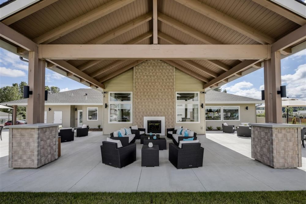 Covered patio with comfortable lounge chairs at LARC at Kent in Kent, Washington