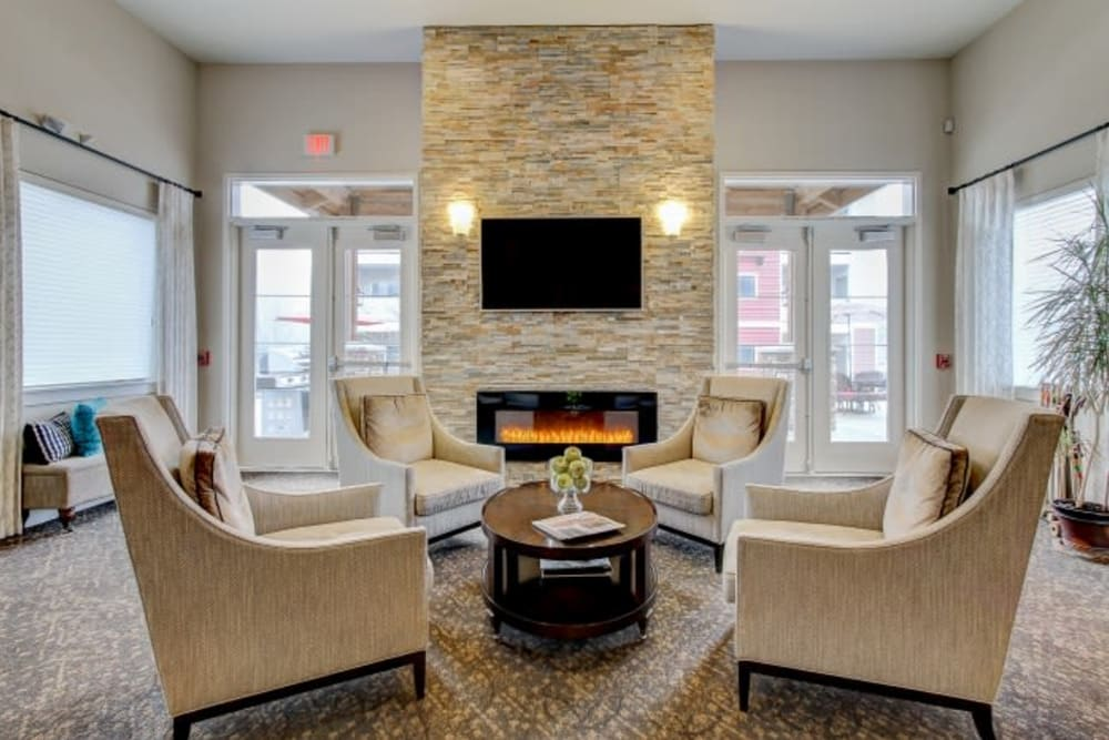 Resident lounge with a fireplace and a flat-screen TV at LARC at Olympia in Olympia, Washington