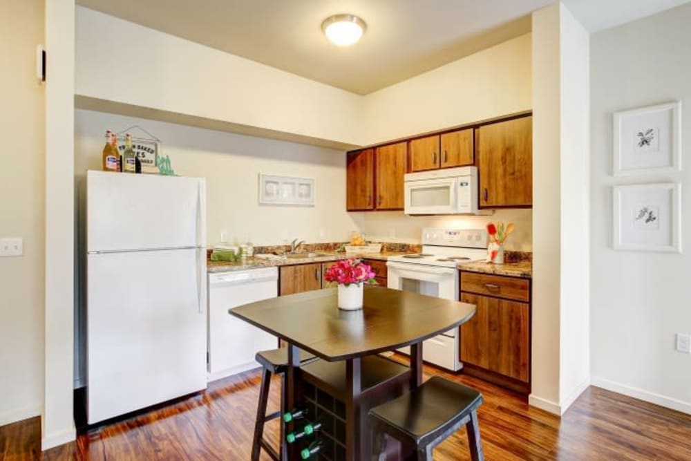 Kitchen with white appliances and wood-style flooring at LARC at Olympia in Olympia, Washington