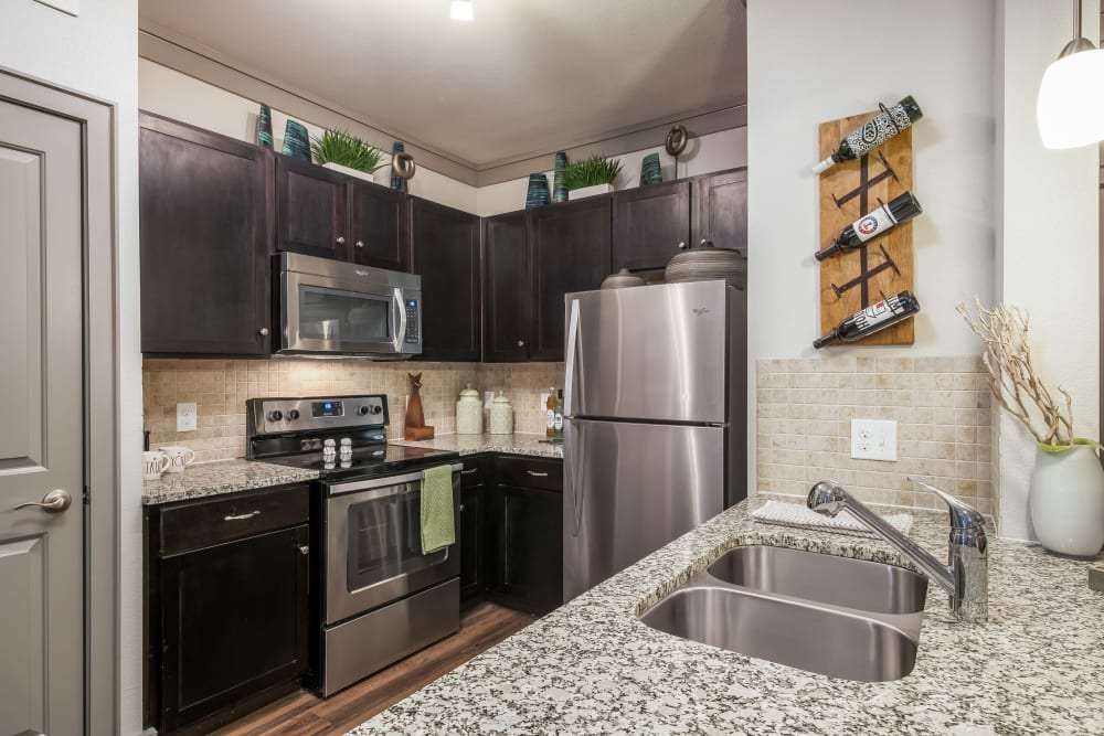 Kitchen with dark cabinets at Sorrel Phillips Creek Ranch in Frisco, Texas