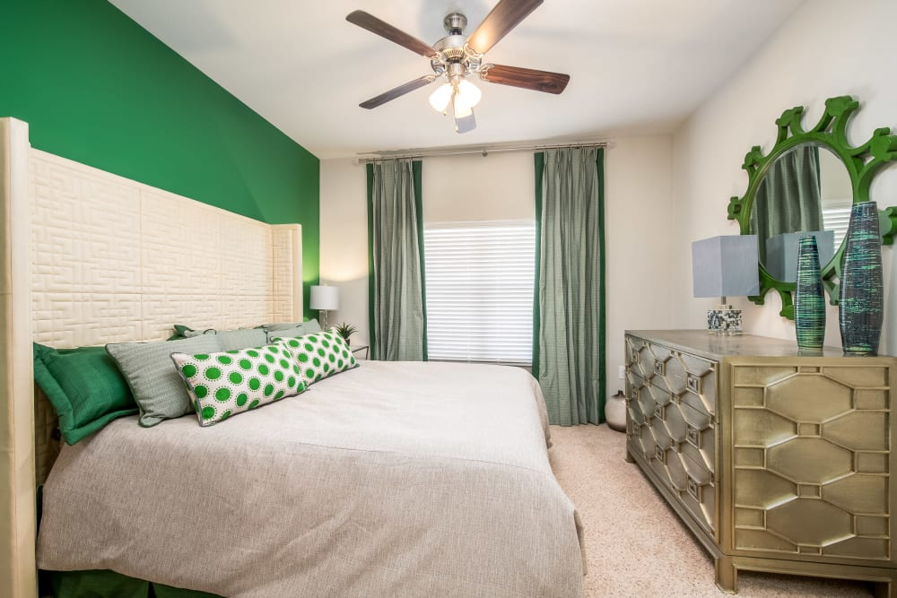 Master bedroom with green accents at Sorrel Phillips Creek Ranch in Frisco, Texas