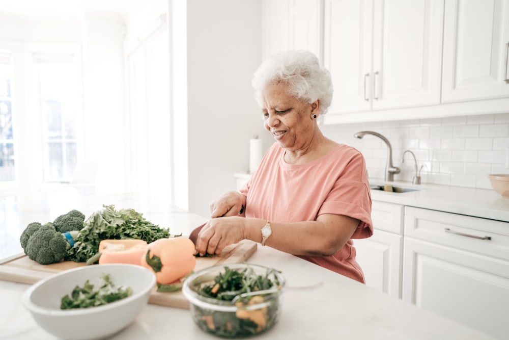 A resident preparing a meal in her kitchen at Carnegie Heights at Henderson in Henderson, Nevada