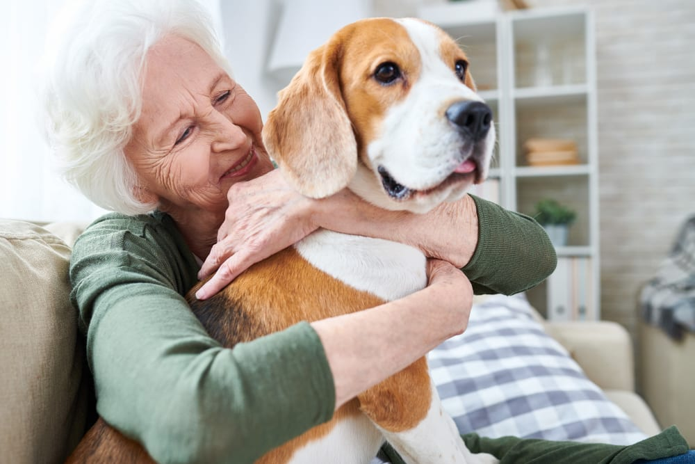 A resident hugging a dog at Carnegie Heights at Henderson in Henderson, Nevada