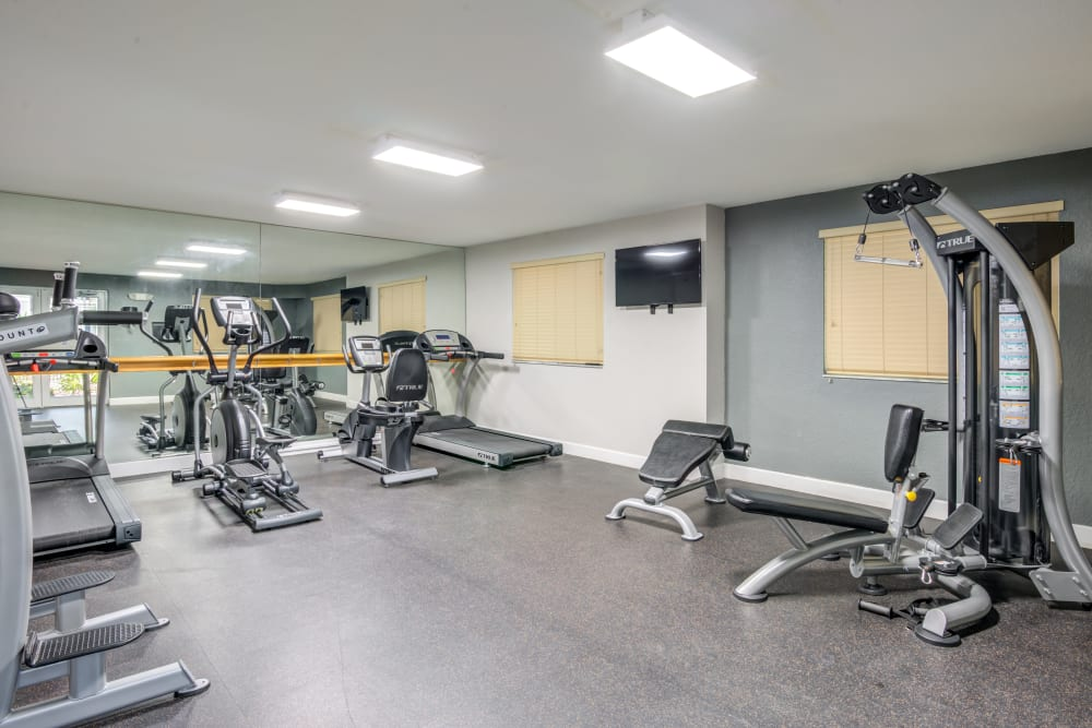 A fitness center with plenty of workout stations at Emerald Dunes Apartments in Miami Gardens, Florida