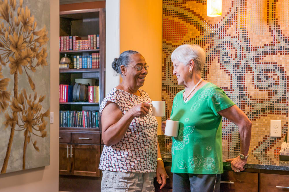 Two residents talking and having coffee together at Watermere at Woodland Lakes in Conroe, Texas