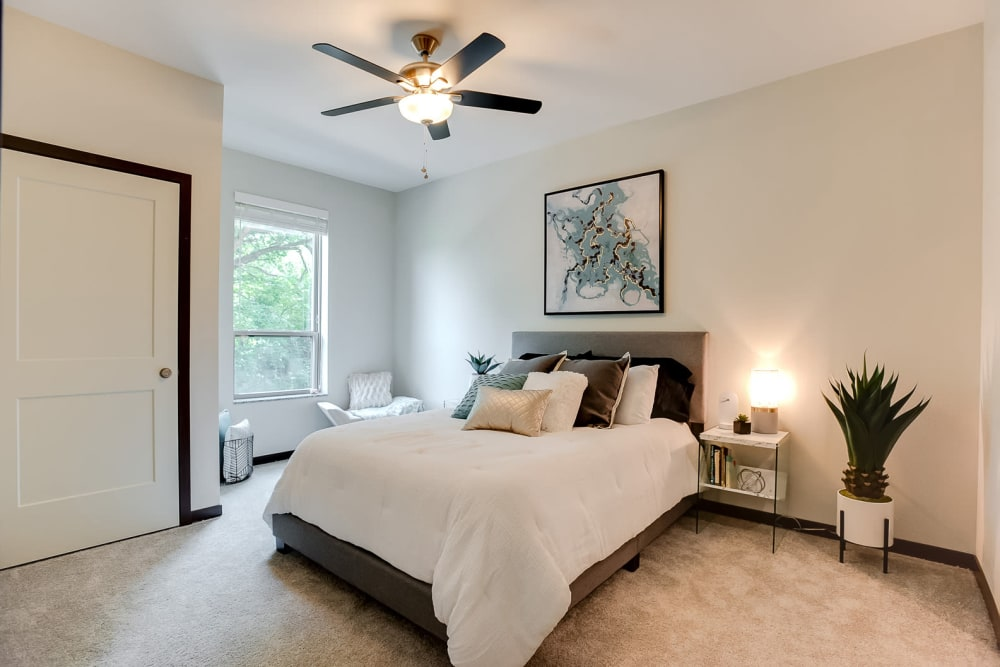 A large bedroom with a ceiling fan and a walk-in closet at Lake Jonathan Flats in Chaska, Minnesota