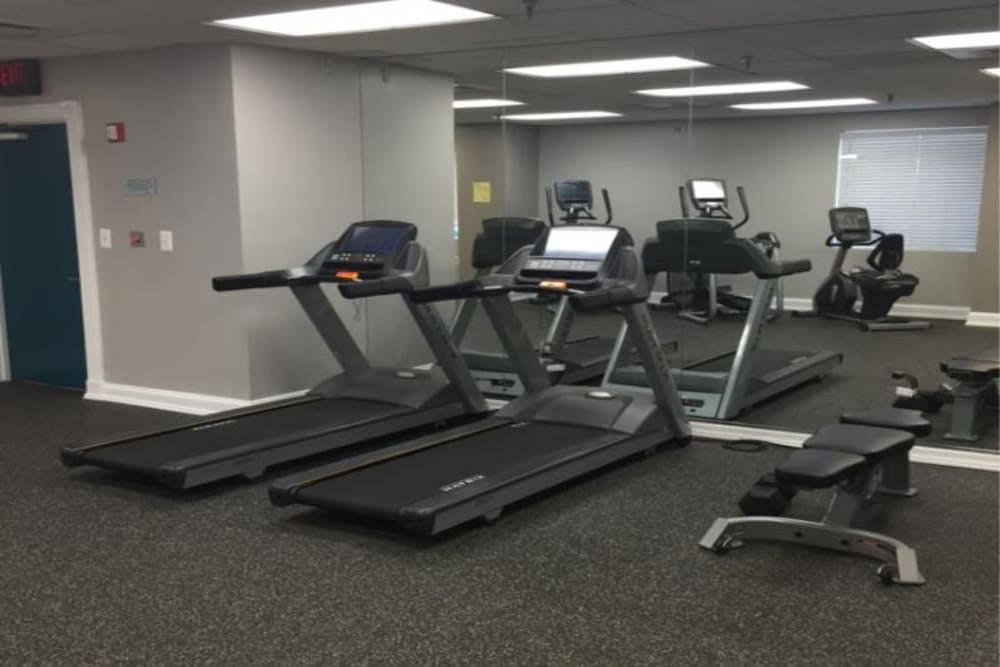 A fitness center with individual workout stations at Westwood Tower Apartments in Bethesda, Maryland
