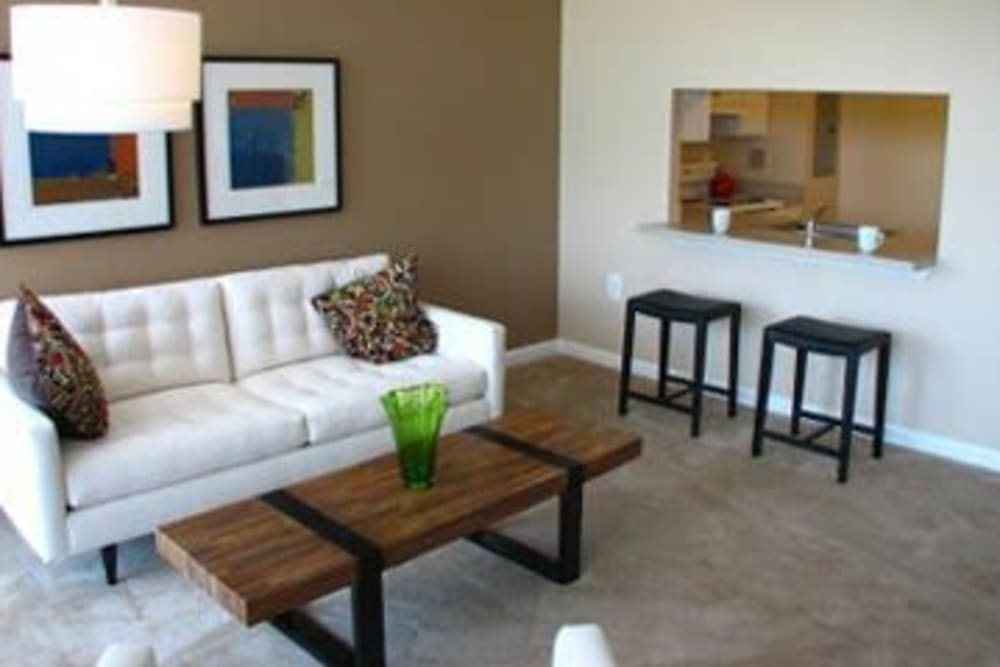 A comfortable living room with kitchen bar seating at Westwood Tower Apartments in Bethesda, Maryland