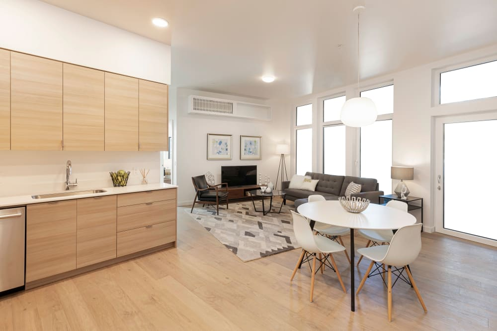 View of the dining and living areas from the kitchen in an open-concept floor plan of a model home at TwentyTwenty Apartments in Portland, Oregon
