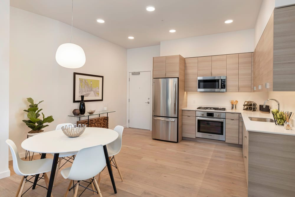 View of the modern kitchen from the dining area in a model home at TwentyTwenty Apartments in Portland, Oregon