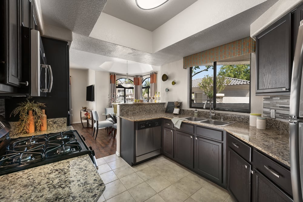 Gourmet kitchen with granite countertops and dark wood cabinetry in a model home at San Pedregal in Phoenix, Arizona