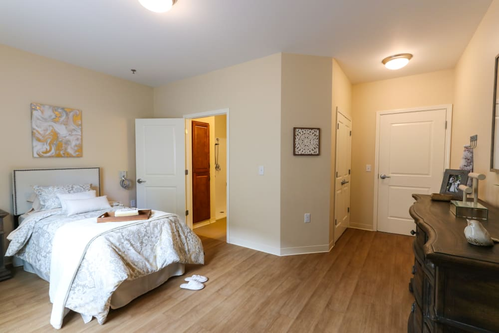 A bedroom with an attached bathroom in a shared apartment at The Harmony Collection at Roanoke - Memory Care in Roanoke, Virginia