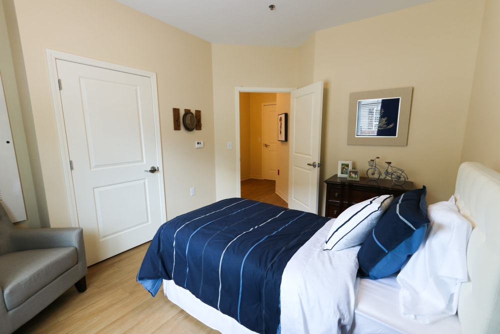 A furnished bedroom in a shared apartment at The Harmony Collection at Roanoke - Memory Care in Roanoke, Virginia
