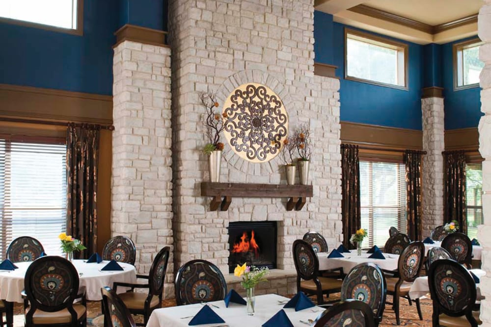 A fire pit with dining tables arranged in front of it at Isle at Cedar Ridge in Cedar Park, Texas