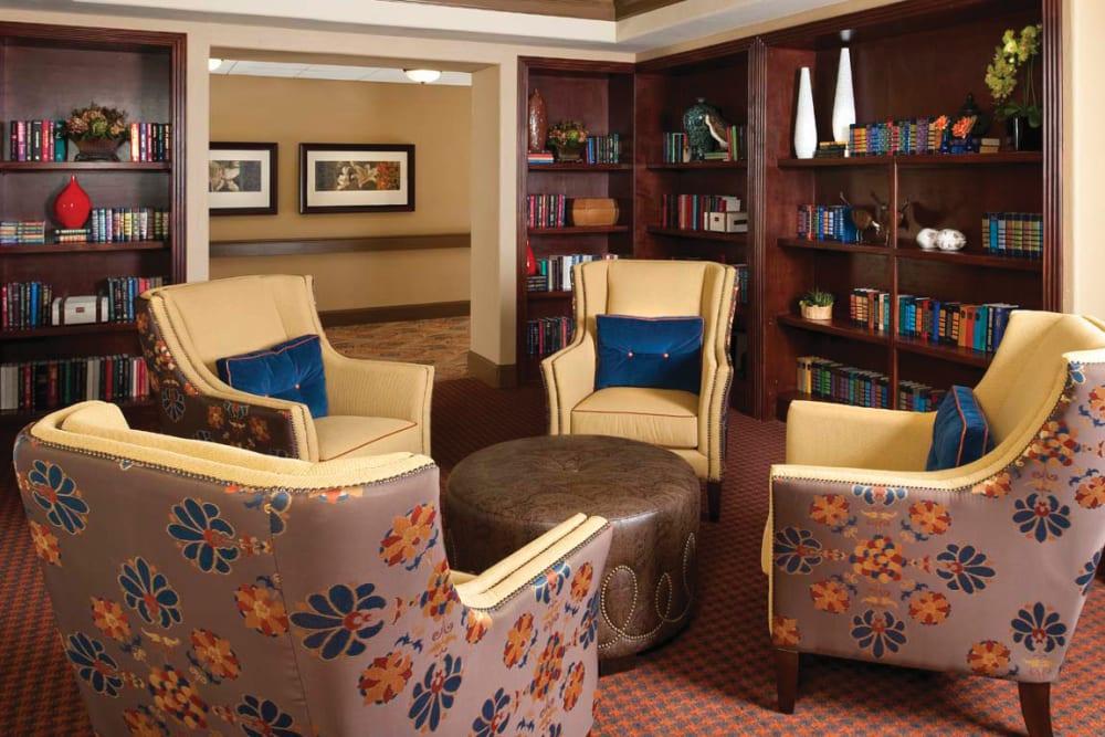 A few couches around an ottoman with a bookshelf behind them at Isle at Cedar Ridge in Cedar Park, Texas