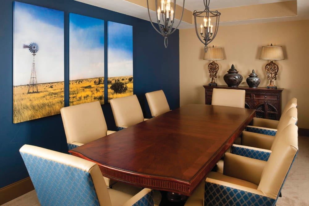 A meeting room with long wooden table and fancy chairs at Isle at Cedar Ridge in Cedar Park, Texas